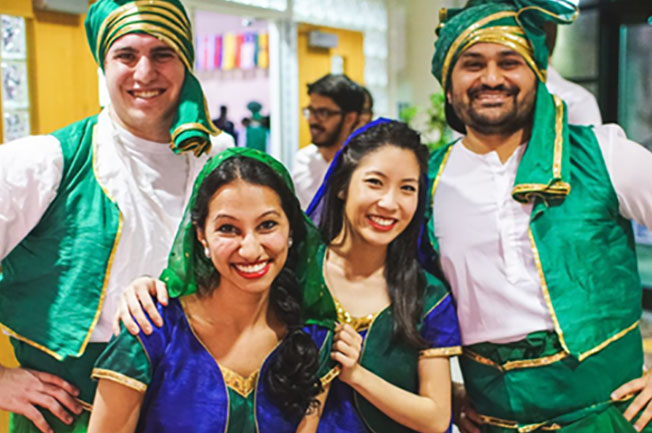 Two male and two female students wear green costumes to celebrate international culture