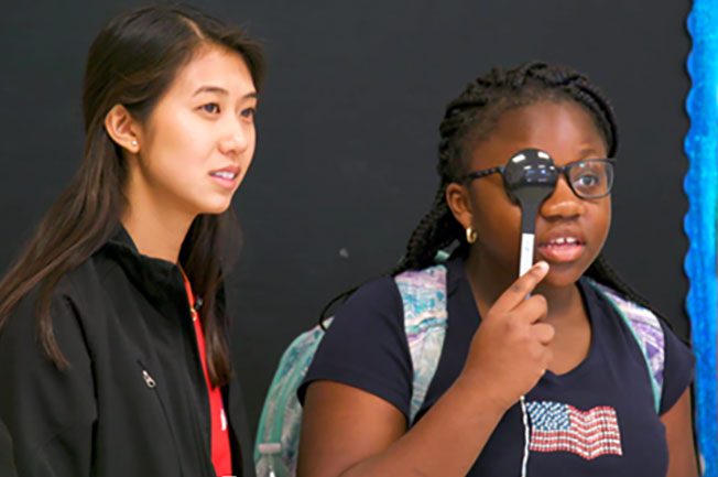 A young girl covers one eye as a female researcher watches