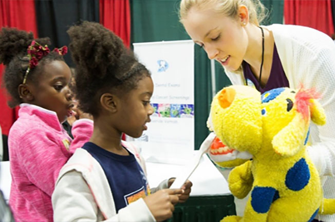 A student uses a large yellow stuffed animal to teach two young girls about brushing their teeth