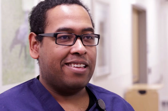 An African American man wearing glasses and wearing a purple scrub shirt