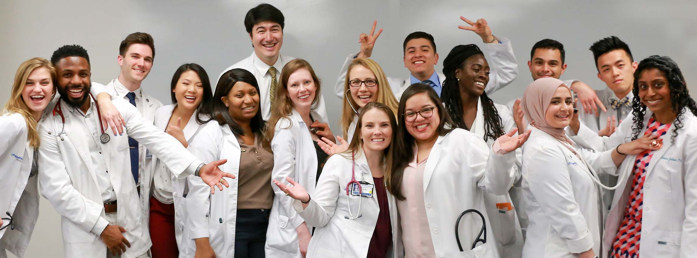A group of 16 students in white coats