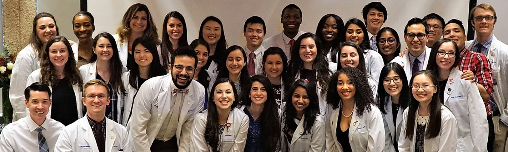 Group of young people in lab coats smiling, with Gold Humanism Honor Society written over them
