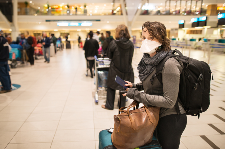 A woman wearing a face mask at an airport