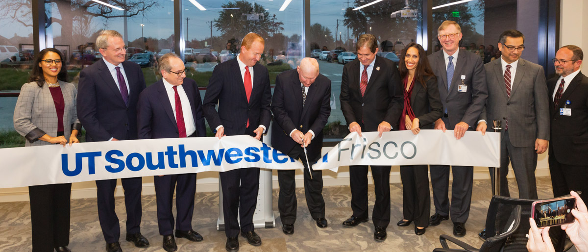 Group of ten people holding a large ribbon that says UT Southwestern Frisco, while person in the middle cuts it with scissors
