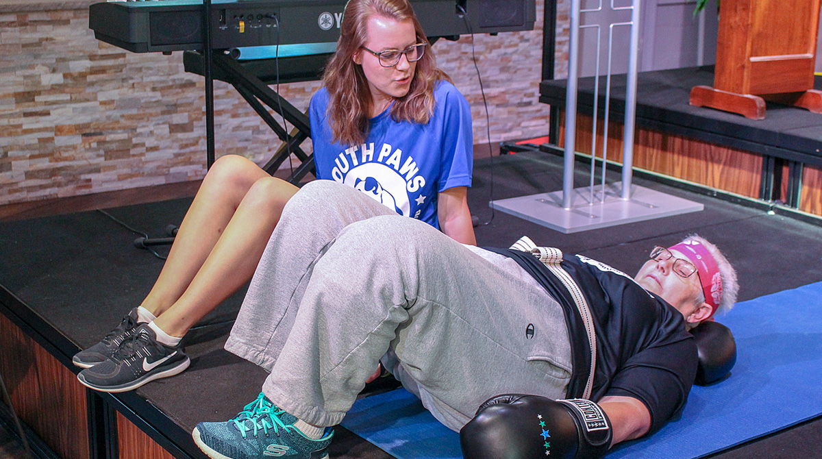PT student assists participant with workout
