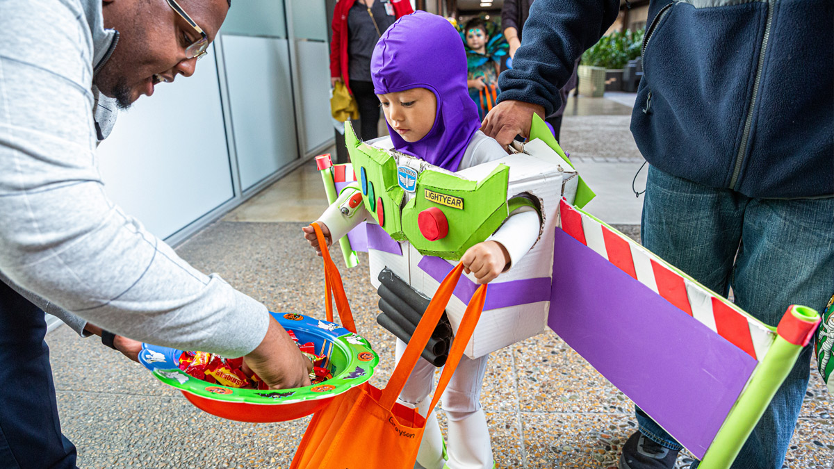 Child dressed as Buzz Lightyear getting candy