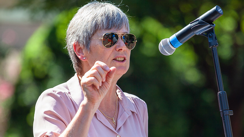 Woman with sunglasses speaking into a microphone