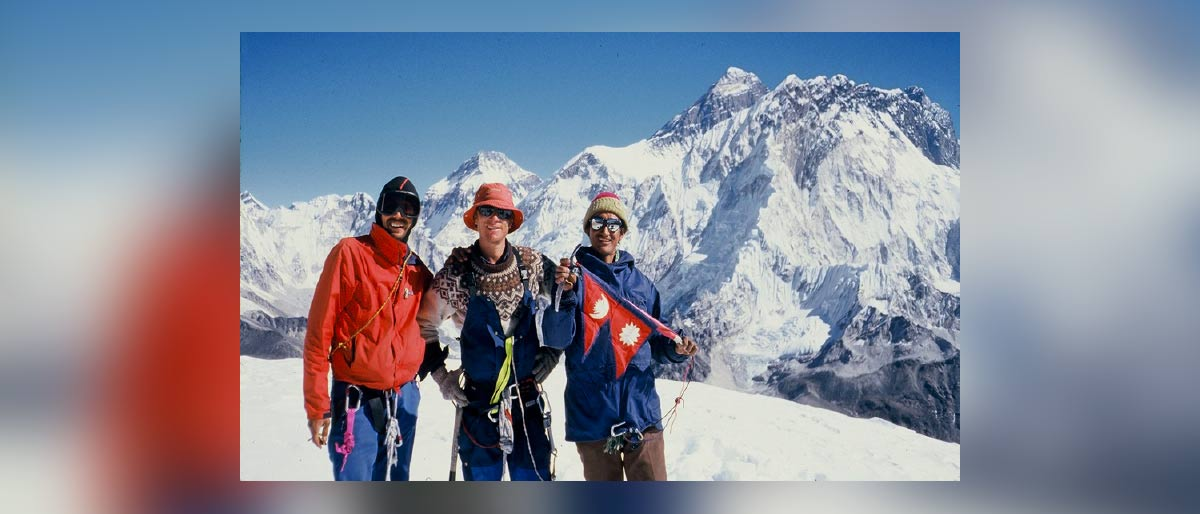 Three men in snow covered mountain area wearing climbing gear