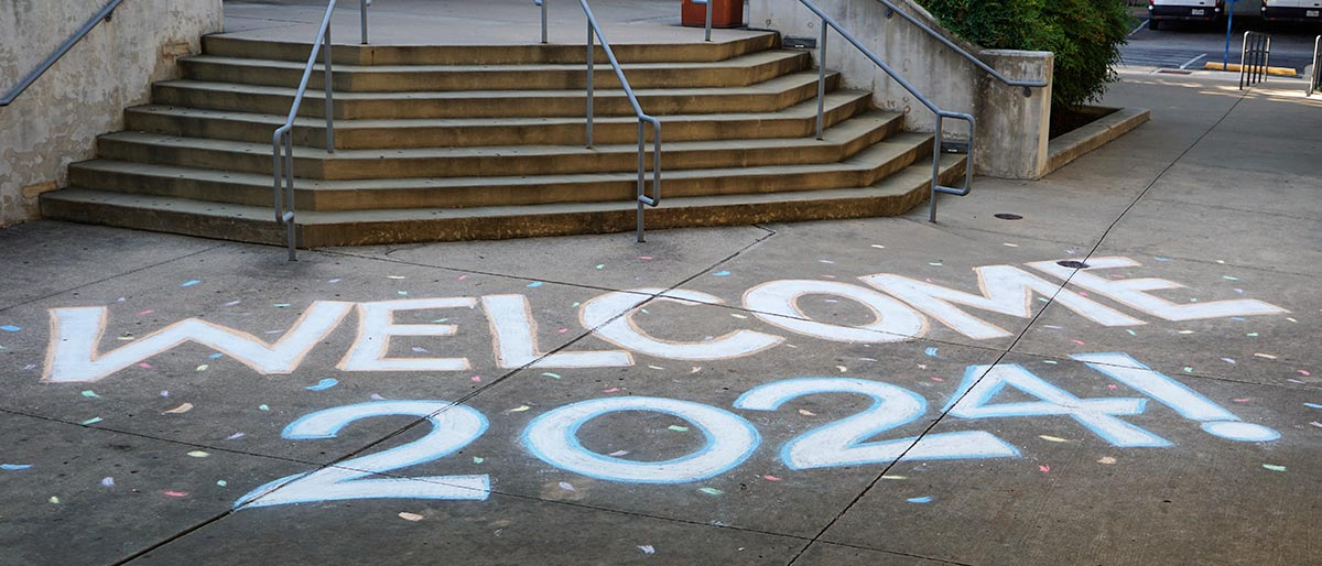 Stairwell entry to buildling, with Welcome 2024 written in chalk