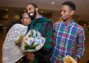 A family squeezes their graduate close after surprising him with flowers.
