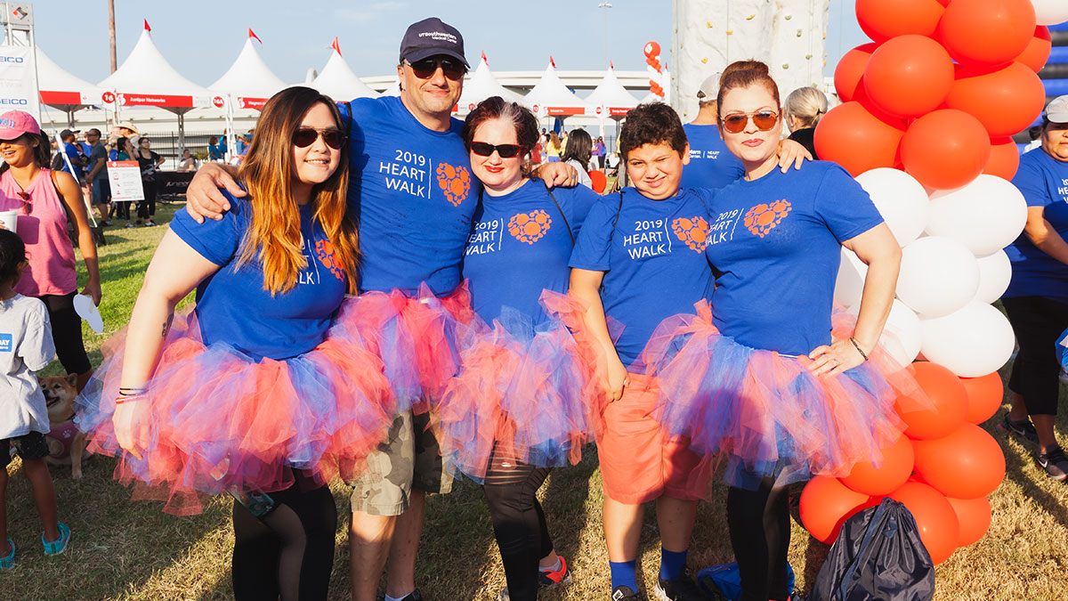 Five people in blue shirts and red tutus attending the Heart Walk