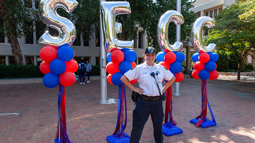 Public safety officer posing in front of balloons in a power stance