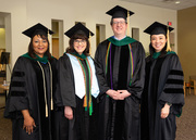 UT Southwestern Medical School Student Affairs Associate Deans Drs. Shawna Nesbitt, Angela Mihalic, Blake Barker, and Melanie Sulistio gather for a photo ahead of the hooding ceremony.