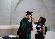 Dr. Evan Wright gets help with regalia from Adrienne Walker.