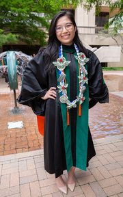 New graduate Dr. Tran Nguyen of Estabrook College poses with her regalia and a special homemade necklace with flowers crafted from dollar bills. She is all smiles about staying at UT Southwestern for her residency.