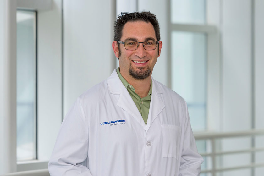 Man with black hair, glasses, goatee in white lab coat