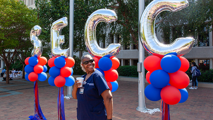 Woman in scrubs standing in front of SECC balloons