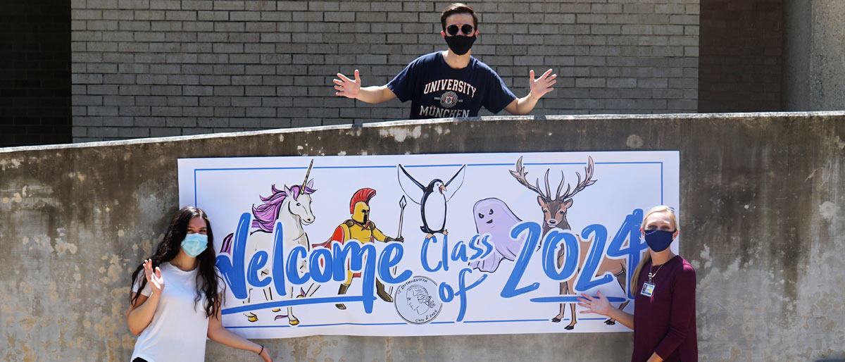 Three students masked, distanced, holding a welcome class of 2024 sign