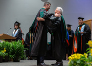 Medical School 2019 Co-Class President Dr. Reed Macy goes in for a hug on stage.