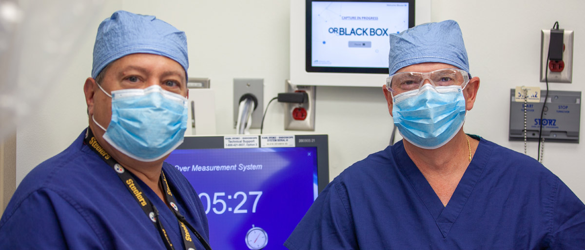 Two men in scrubs, surgical masks
