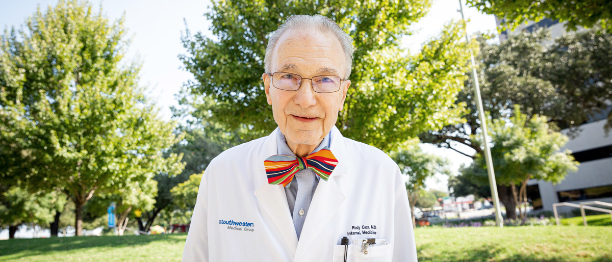 Older man in lab coat with a red bow tie