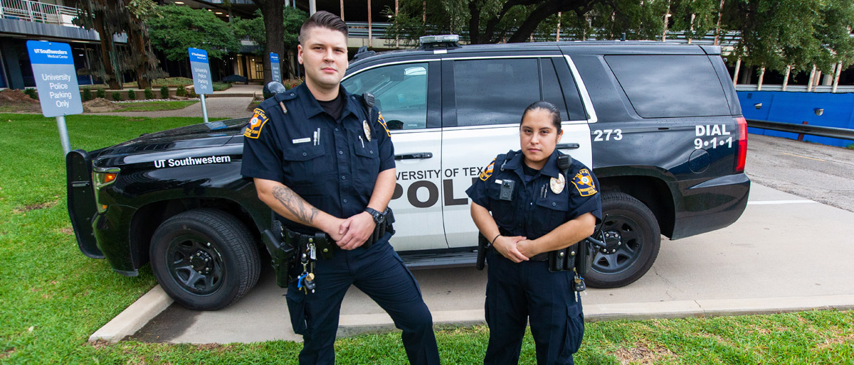 Two uniformed officers in front of a UT police vehicle