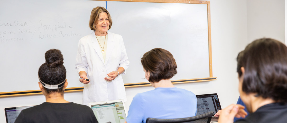 Woman dressed in white teaching a class