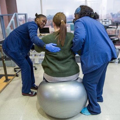 Two women in scrubs assist a patient sitting on a yoga ball