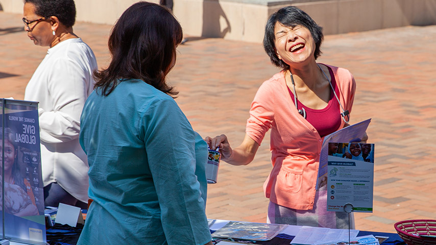 Woman laughing and smiling while donating