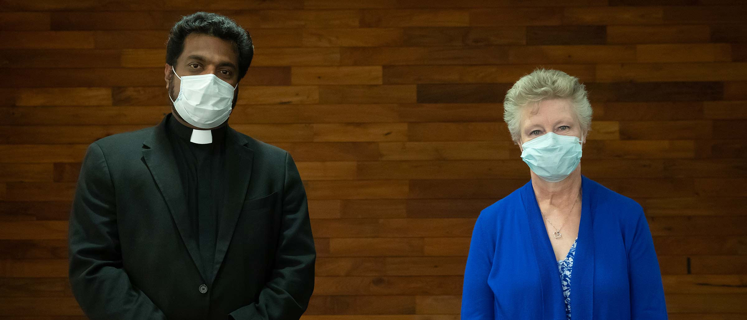 Man in black jacket and priest's collar and woman in blue, wearing masks and standing apart, in wood paneled room