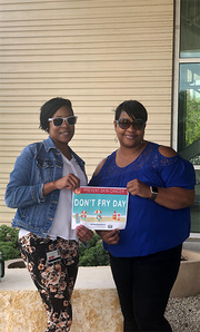 Treeca Pate and Tyesha Brown of Radiation Oncology enjoy lunch outside on a partly sunny, windy day.