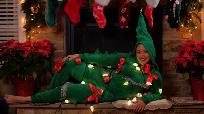 Woman dressed in green onesie covered in bows and lights reclining on a fireplace