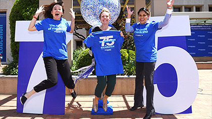 Employees jumping to celebrate the school's 75th anniversary