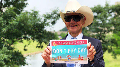 Man in cowboy hat and sunglasses holding up a sign that says Don't Fry Day