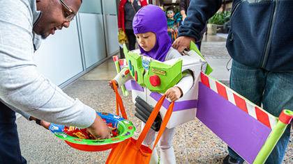 Child dressed as Buzz Lightyear picking candy