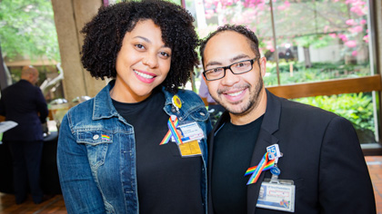 Man and woman wearing rainbow pride ribbons on their lapels