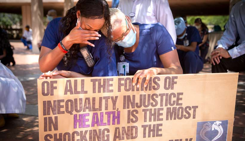 Two women in scrubs and masks, holding a sign that reads Of all the forms of inequality, injustice in health care is the most shocking and inhumane