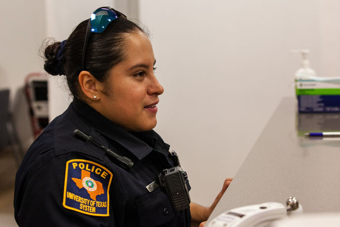 Officer wearing uniform and sunglasses on her head in a hospital room