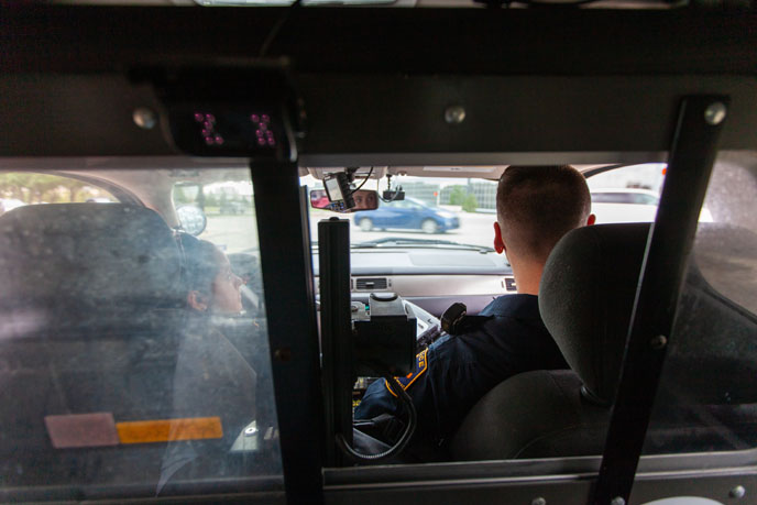 View from the back of a patrol car, two police officers sitting up front