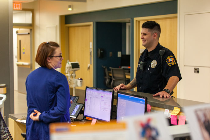 Police officer talking to person at nurse's station