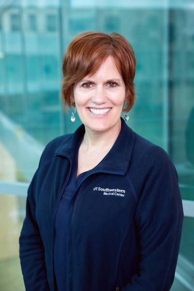 Woman with brown hair, blue collared UTSW shirt
