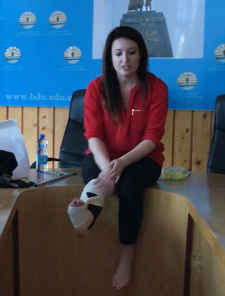Woman in a red shirt wrapping her foot in a demonstration