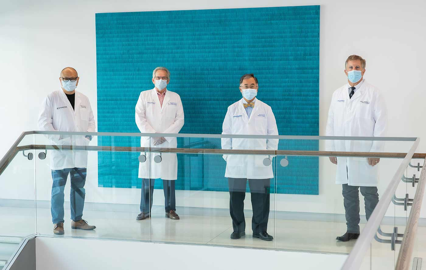 Fourp men in lab coats, wearing masks, spaced apart