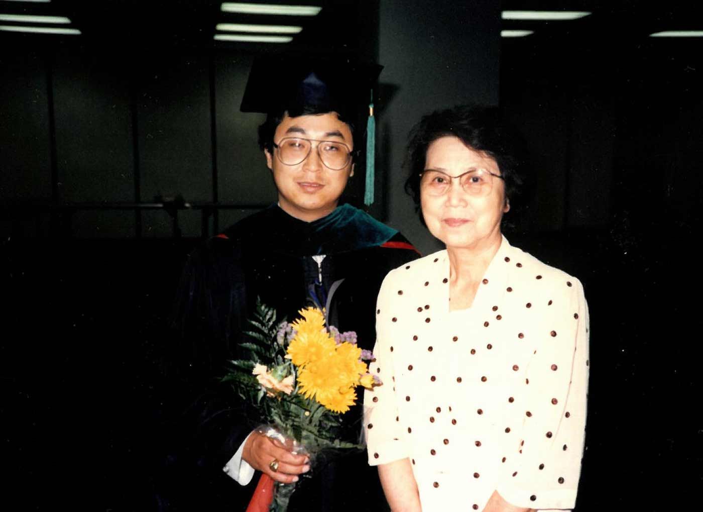 Man in graduation gown with woman in dotted dress