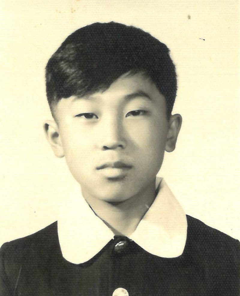 Young boy with short hair, wearing black shirt with white collar.