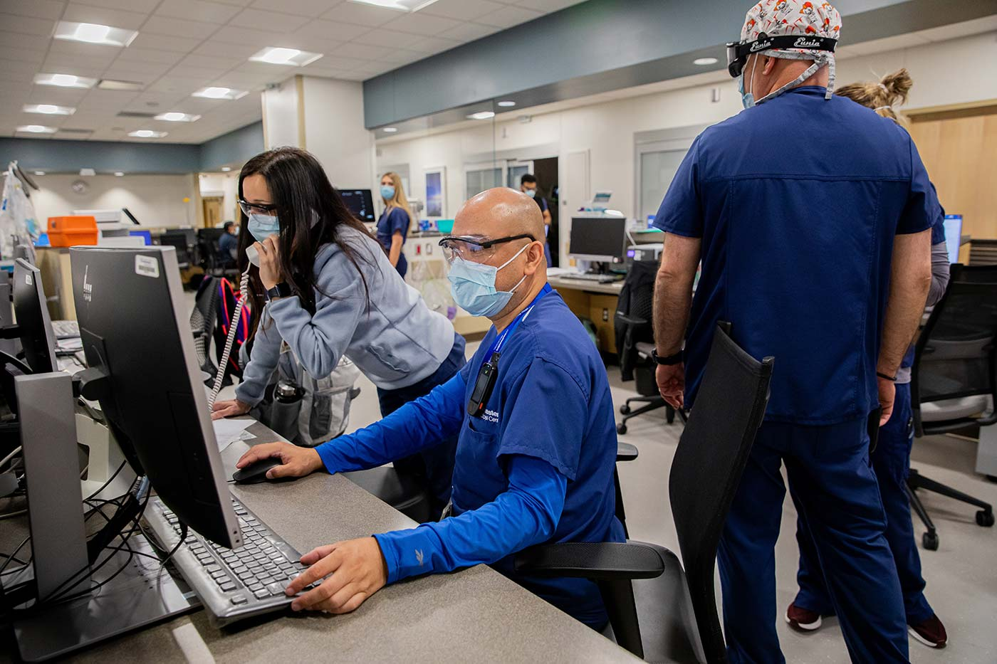 People in scrubs and masks working at computers