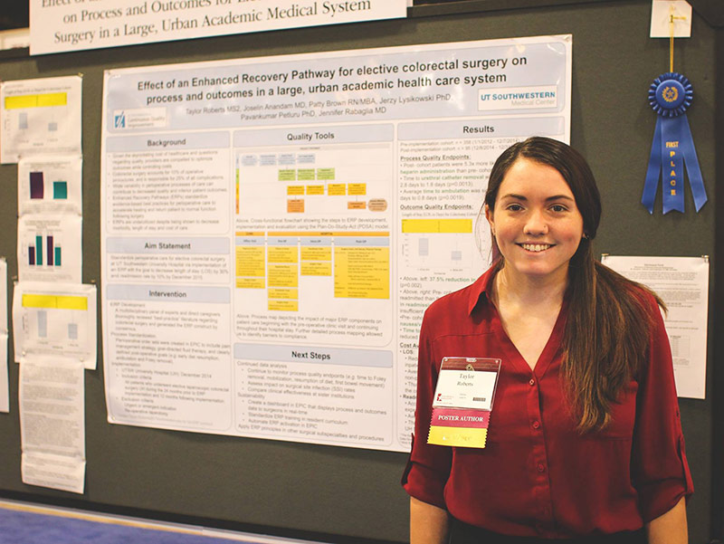 Woman in red shirt standing by research poster
