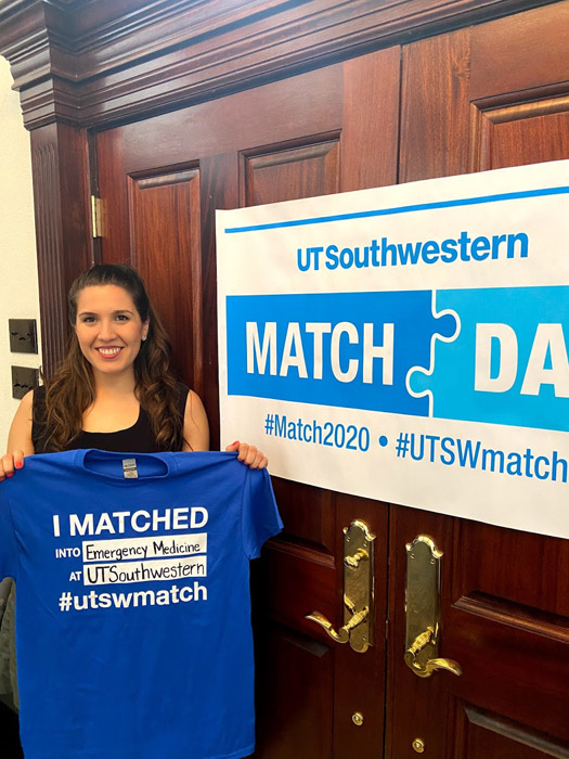 Woman holding shirt with match day information on it