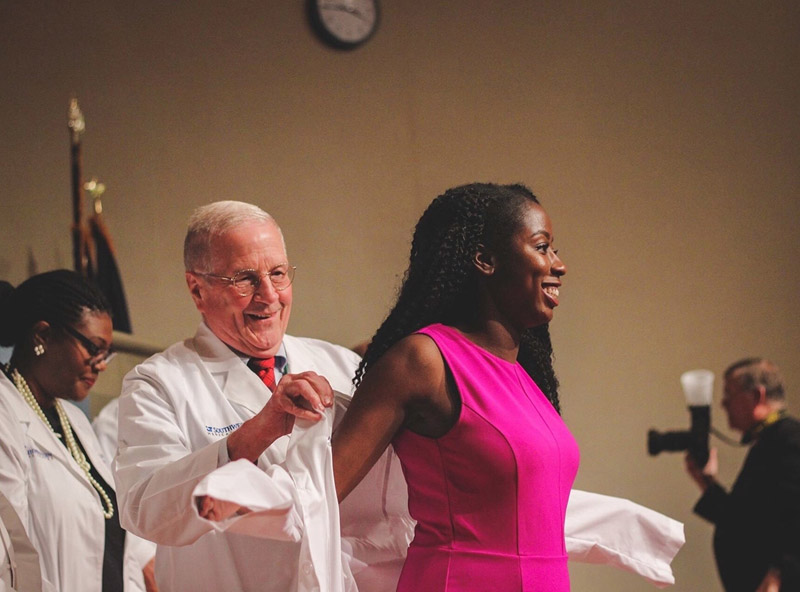 Woman in pink dress donning on a white lab coat on a stage