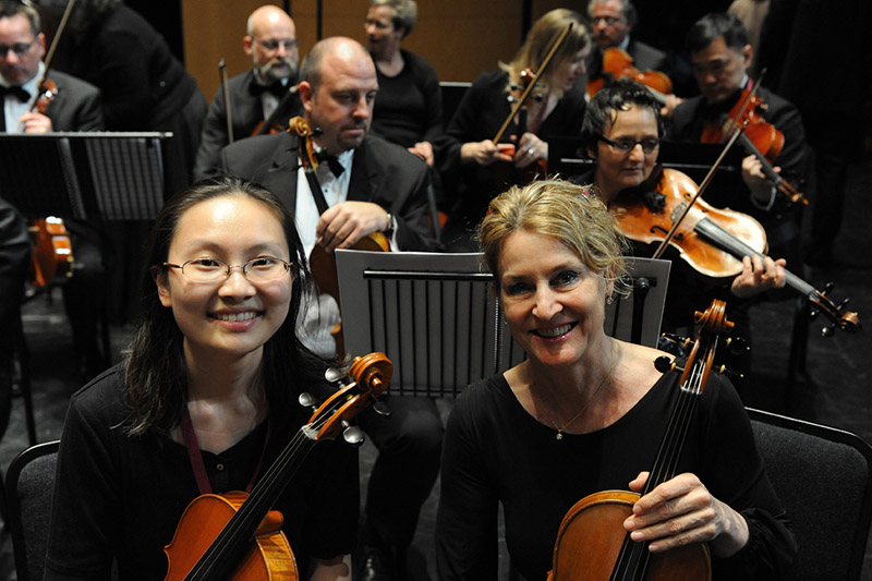 Two women holding violins smiling